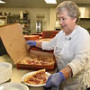 Brad Davis/The Register-Herald<br /> Volunteer Lucy Terry grabs a couple slices of pizza for someone as she works in the kitchen during Little Ceasars Love Kitchen's visit to Fishes & Loaves behind the Church of God Family Worship Center Saturday morning. Little Ceasars provided enough pizza to feed over 1,000 people, with more than 800 attending the event throughout the morning.