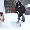 Rick Barbero/The Register-Herald<br /> Sharon Duncan shovels her sidewalk with her dog Katie on Westwood Drive in Beckley Friday morning.