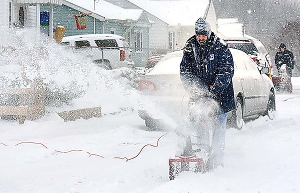 Rick Barbero/The Register-Herald<br /> James Hunter, left and Johnathan Cruise, clear snow off sidewalks on Westwood Drive in Beckley Friday morning.