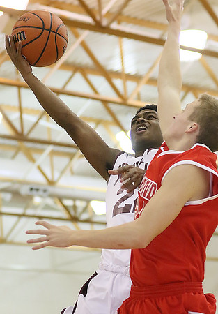 Brad Davis/The Register-Herald<br /> Woodrow Wilson's Isaiah Francis drives to the basket as Cabell Midland's Jason Gibson defends during the Flying Eagles' win over the Knights Saturday night in the Woodrow gym.