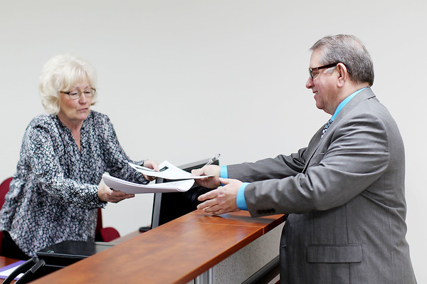 Raleigh County Circuit Clerk Paul Flanagan, right, hands deputy clerk Kathy Lovell his files on the first day of candidates filing for office at the Voter Registration Building in Beckley on Monday.