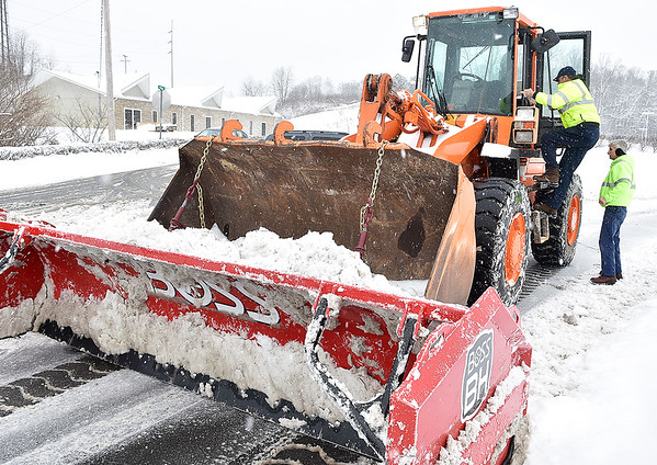 Brad Davis/The Register-Herald<br /> West Virginia Parkways Authority worker James Shuck climbs into a massive bulldozer for his turn as fellow worker Mike Miller finishes up a shift while the two work to clear the driveways around Tamarack Saturday afternoon.