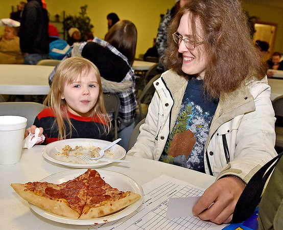 Brad Davis/The Register-Herald<br /> Beckley residents Katrina Kennedy and her 4-year-old daughter Sarah enjoy a hot breakfast and pizza during Little Ceasars Love Kitchen's visit to Fishes & Loaves behind the Church of God Family Worship Center Saturday morning. Little Ceasars provided enough pizza to feed over 1,000 people, with more than 800 attending the event throughout the morning.