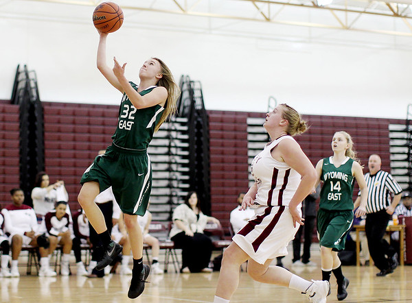 Wyoming East's Gabby Lapardus (32) goes up for a layup as Woodrow Wilson's Paige Lewis (22) chases during their basketball game Monday in Beckley.