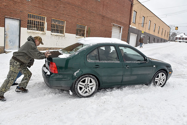 Brad Davis/The Register-Herald<br /> Good sumaritans Kenneth Shrewsburry, near, and Roy Lester (behind Shrewsburry) give a push to struggling motorists as they try to make their way up Center Street Friday afternoon.