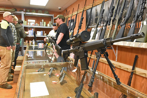 Brad Davis/The Register-Herald<br /> Firearms sit on display at Shooter's Roost on Kanawha Street as owner Eric Stratton (background right) talks to customers Wednesday afternoon.