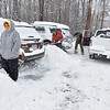 Brad Davis/The Register-Herald<br /> Beckley resident Beverly Decoster, left, looks on and gladly accepts help from good sumaritans Roger Kidd, middle, and Garret Tomlin, right, as they dig her and other residents' vehicles out at a Maxwill Hill Road apartment complex Saturday afternoon. Kidd and Tomlin spent the day driving around, plowing and digging out anyone who needed the help.