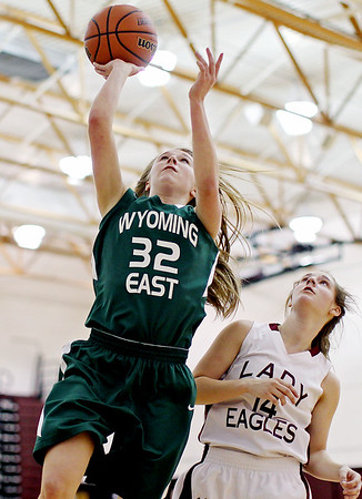 Wyoming East's Gabby Lupardus (32) scores a layup while being fouled by Woodrow Wilson's Lyric Moon (14) <br /> during their basketball game Monday in Beckley. Lupardus scored the free-throw.