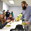 Brad Davis/The Register-Herald<br /> Brandon Richardson (right), founder of Headwaters Defense, hands out printed copies of Fayette County's fracking waste and storage ban to attendees during a celebration of the ordinance's passing Tuesday night at Brethren Fellowship Center in Oak Hill.