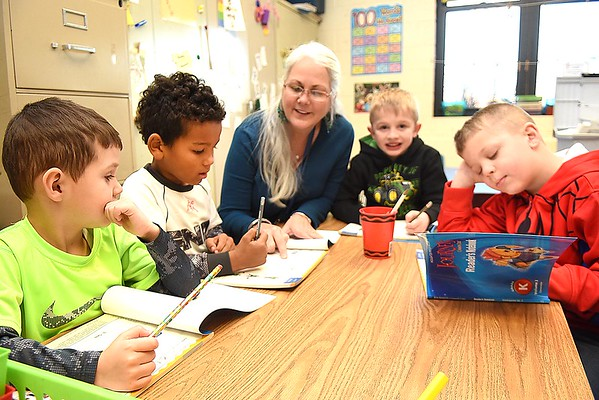 Rick Barbero/The Register-Herald<br /> Karen Greer, kindergarten teacher, third from left, works with her students, Nolan Selter, left, Jabari Spencer, Mason Whitener and Ben Fitzwater after returning back from Christmas break. Children returned back to school Tuesday morning a little sluggish and with some anxiety explained, Crescent Elementary School principal Theresa Lewis. The children are just out of their routine bit because the past 13 days they've been staying up later, sleeping later and staying in their pajamas longer. Lewis said we just greet them with a smile and give them a big warm hug and by mid day they are back to normal.