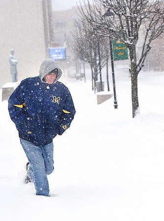 Rick Barbero/The Register-Herald<br /> Ronnie Allman, of Beckley, walking on snow covered sidewalks on Neville Street in Beckley Saturday morning on his way to work at McDonalds. The winter Storm Jonas blasted the area with approximately 16 inches of snow.
