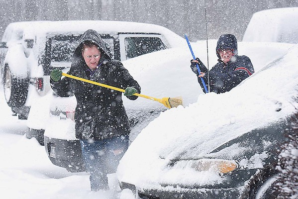 Rick Barbero/The Register-Herald<br /> Danielle Zadora, of Rochester, Ny,, left, helps her mother, Cindy Zadora, of Laurel, NC, clean snow off her car on the parking lot of Country Inn & Suites on Harper Road in Beckley, WV Saturday morning. The winter Storm Jonas blasted the area with approximately 16 inches of snow.