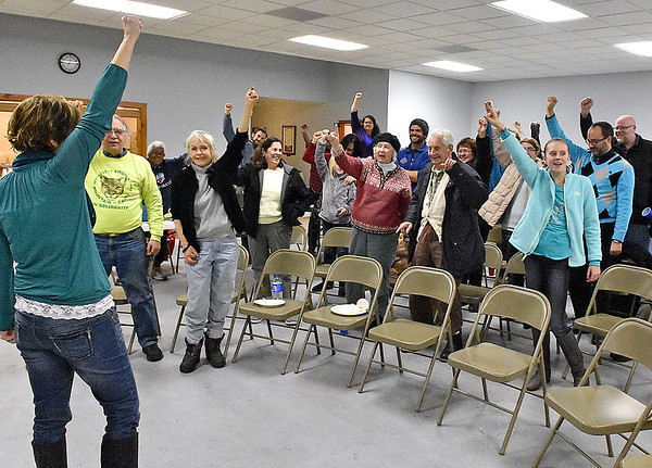 Brad Davis/The Register-Herald<br /> Headwaters Defense member and Fayette County teacher Kristine Gilkey, far left, encourages area residents in attendance to raise their arms in celebration after the county passed an ordinance banning fracking waste from being stored or disposed of Tuesday night in Oak Hill. Several members of surrounding communities, county teachers, local leaders and activists gathered at the Brethren Fellowship Center to celebrate the ordinance, enjoy some food and take in some tunes by local musicians.