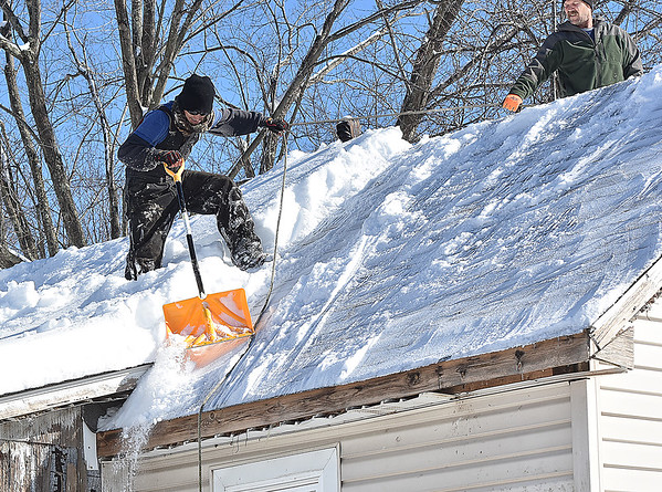 Brad Davis/The Register-Herald<br /> Chad Minor holds on to a rope to keep from slipping off as he carefully removes snow from the roof of a Stanaford Road residence with help of Lee Dawson, who holds the rope for him Sunday afternoon. Sunday's sunny weather was great for melting off a portion of thew weekend's snow, but it also made remaining snow heavy and burdensome on the roofs of many homes, creating a need to remove it if possible.