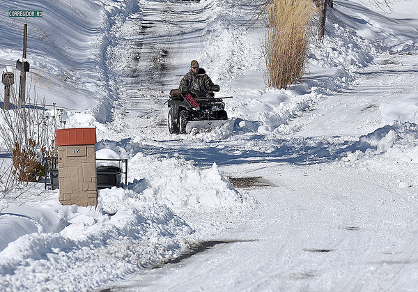 Brad Davis/The Register-Herald<br /> An ATV-riding snow plower clears driveways in a residential area off Stanaford Road Sunday afternoon.
