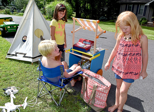 "(Brad Davis/The Register-Herald) Beckley residents Liam Lefler (sitting), 9, his sister Katelynn (right), 7, and neighbor Hannah West, 8, man their well-stocked drink stand as the trio sells them for a dollar each along Bluff Road Friday afternoon. The youngsters set up a tepee, brought a couple of hermit crabs to keep them company (in the bowl right of the register) made good use of a toy cash register and drove up and down neighborhood streets in their ""company car"" (the powerwheel at far left) holding signs as they spent around three hours of the hot day selling cold bottles of water, cans of soda and even V8 in an effort to raise money to donate to flood relief efforts around the state."