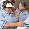 (Brad Davis/The Register-Herald) Volunteers Sherrie Hunter and her husband David, this year's tournament honorees, work tirelessly to keep track of the action during Monday's final round of the BNI Monday afternoon on the Cobb Course at Glade Springs.