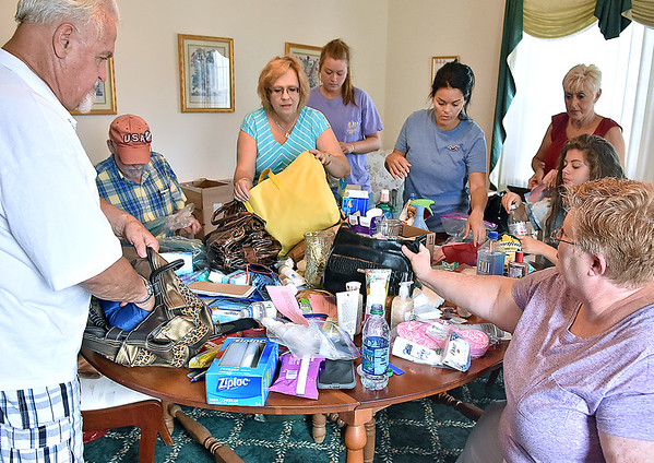 (Brad Davis/The Register-Herald) Volunteers from First Baptist Church pack donated purses full of items Friday evening at the Neville Street church. From left are, James Calhoun, Russ Parsons, program founder Donna Miller, Taylor Blankenship, Erica Cole, Ginger Cole, Brooke Cole and Kathy Ann Plumley (lower right).