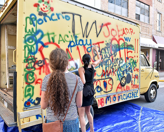 (Brad Davis/The Register-Herald) Attendees stop to quickly add to a truck serving as a mobile graffiti canvas as they pass by during Theatre West Virginia's Beckley First Friday event yesterday evening on Main Street.