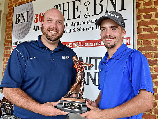 (Brad Davis/The Register-Herald) United Bank's Jeff Miller, left, presents the championship trophy to this year's winner Cole Moore following Monday's final round of the BNI Monday afternoon on the Cobb Course at Glade Springs.