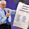 (Brad Davis/The Register-Herald) Chairman Tex Williams holds up a sign bearing the names of area sports legends who've passed away since the 2009 reunion during the annual Jack Lilly Sports Legends dinner Saturday night at the Beckley Moose Lodge. The list doesn't yet include the late Mickey Furfari, who passed just a few days earlier.