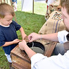 "(Brad Davis/The Register-Herald) Three-year-old Micah Walters gets a little help from WVU Extension Services' Joe Obidzinsky in dipping a wick in hot wax while making a candle Saturday afternoon at the Youth Museum's Mountain Homestead. WVU Extension Services sent its traveling ""History in a Wagon"" program from their Jackson's Mill location to give youngsters an idea of the type of activities and lives early pioneers experienced. Kids learned how to make rope and candles the same way early settlers would have."