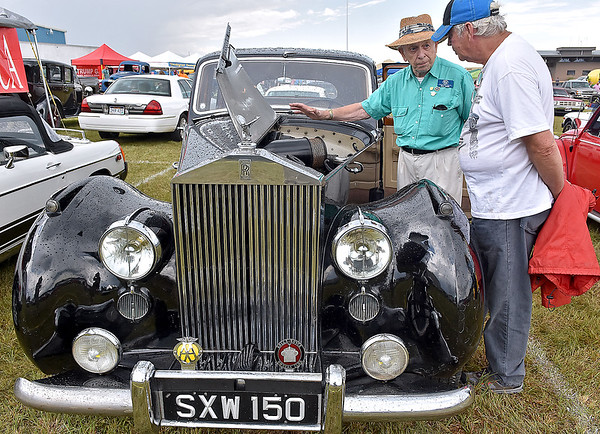 (Brad Davis/The Register-Herald) Owner Bill Bibb, left, shows off his 1953 Rolls-Royce Silver Dawn to Beaver resident Dame Simmons at the Friends of Coal Auto Fair Saturday afternoon at the Raleigh County Memorial Airport. Bibb said his specific Silver Dawn is number 18 out of only 25 that were ever built.