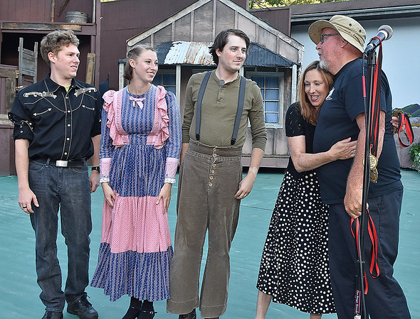 (Brad Davis/The Register-Herald) At right, Barbie Yurick hugs Theatre West Virginia's Scott Hill as he presents her and her three children (from left) Sam, Alice and Nick with the late John Yurick's hall of fame medal prior to Saturday night's opening performance of Hatfields & McCoys at Grandview Park's Cliffside Amphitheatre.