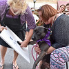 (Brad Davis/The Register-Herald) Operation Underdog's Shawna Shockney, right, holds up Janice's painted paws as 110 Marshall's Linda Boydpresses them to a canvas to make flower paintings from the prints during Theatre West Virginia's Beckley First Friday event yesterday evening on Main Street. Janice is currently in foster care with Operation Underdog and is fully adoptable.