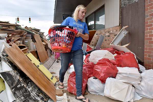 (Brad Davis/The Register-Herald) Rainelle resident Chanda Jordan makes her way through a maze of stacked debris along a sidewalk as she carries donated clothing and child care items up to her Main Street apartment Sunday afternoon. She and her husband Van had just moved up to West Virginia from North Carolina a short time ago and had finalized the purchase of a home on the edge of town just a few of days before it was destroyed by last week's historic flooding, trashing their belongings with it. The couple has two kids of their own, are adopting two within the family and recently received news of another on the way.