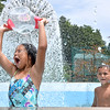 (Brad Davis/The Register-Herald) Seven-year-old Beckley resident Ava Delorso, left, douses herself with chilly water while brother Luis, right, watches as they and other siblings spend a hot Friday afternoon trying to stay cool in the fountain at the 2nd Street park. She, sister Alana, 9, and brothers Brayden, 4, and Luis, 5, spent at least a couple of hours splashing around in the fountain, which on a day like yesterday served as more of a giant sprinkler.