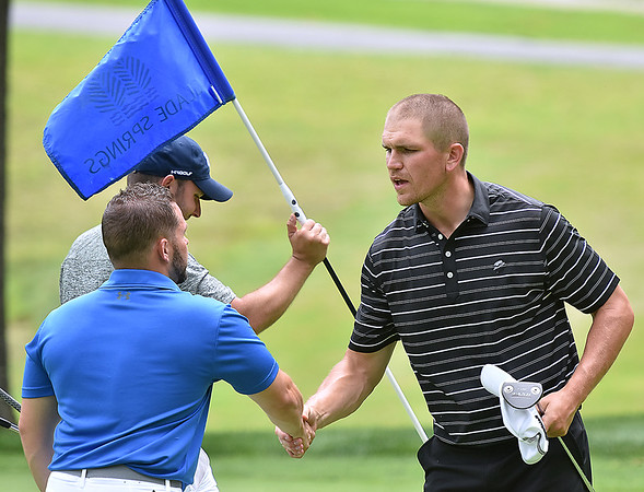 (Brad Davis/The Register-Herald) Tyler Bullington, right, congratulates groupmates J.R. Scott, left, and Nick Mays (holding flag) following Monday's final round of the BNI Monday afternoon on the Cobb Course at Glade Springs.
