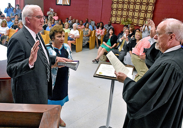 (Brad Davis/The Register-Herald) Beckley Mayor-elect Rob Rappold, left, is sworn in by Judge Robert Burnside, right, during a ceremony at City Hall Thursday evening.