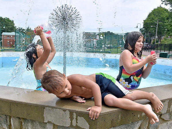 (Brad Davis/The Register-Herald) No swimming pool nearby? No problem for youngsters (from left) Ava, 7, Brayden, 4, and Alana Delorso, 9, who along with their little brother Luis (unphotographed) took advantage of the cool waters flowing in the fountain at the Thornhill Courts park along 2nd Street Friday afternoon. With temperatures around 90 again, anything nearby that funtioned as a massive sprinkler, such as the 2nd Street Park's fountain, was bound to draw anyone looking to stay cool through the day.