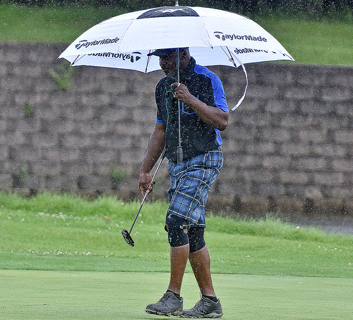 (Brad Davis/The Register-Herald) Ken Fleming uses an umbrella while looking over his next putt  while playing through rain during BNI Classic action Saturday afternoon at Brier Patch Golf Links.