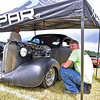 (Brad Davis/The Register-Herald) Staying out of a brief rain shower at the Friends of Coal Auto Fair Saturday afternoon at the Raleigh County Memorial Airport.