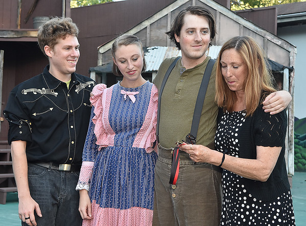 (Brad Davis/The Register-Herald) At right, Barbie Yurick holds back a ferw tears as she and her three children (from left) Sam, Alice and Nick look over their late father John Yurick's hall of fame medal after receiving it during a ceremony prior to Saturday night's opening performance of Hatfields & McCoys at Grandview Park's Cliffside Amphitheatre.