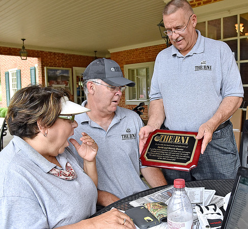 (Brad Davis/The Register-Herald) Volunteers Sherrie Hunter and her husband David, this year's tournament honorees, are presented with a special plaque by Beckley Newspapers Publisher Frank Wood following Monday's final round of the BNI Monday afternoon on the Cobb Course at Glade Springs.