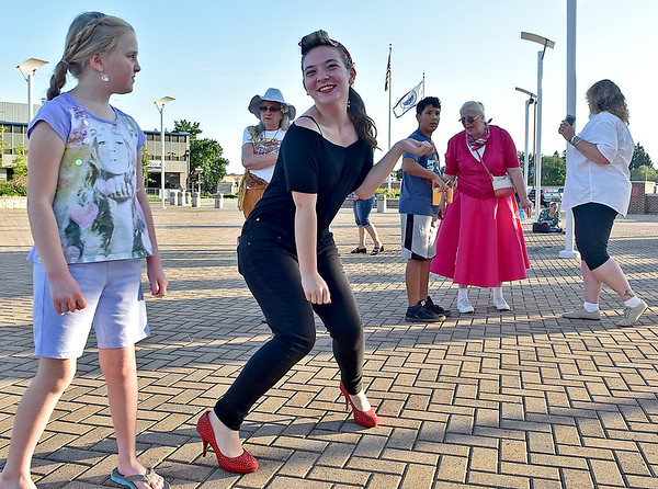 (Brad Davis/The Register-Herald) Some observe while others, like 18-year-old Samantha Ingram (middle), bust a few moves during a Sock Hop dance celebration and United Way of Southern West Virginia shoe and sock drive Friday evening on the Beckley Intermodal Gateway.