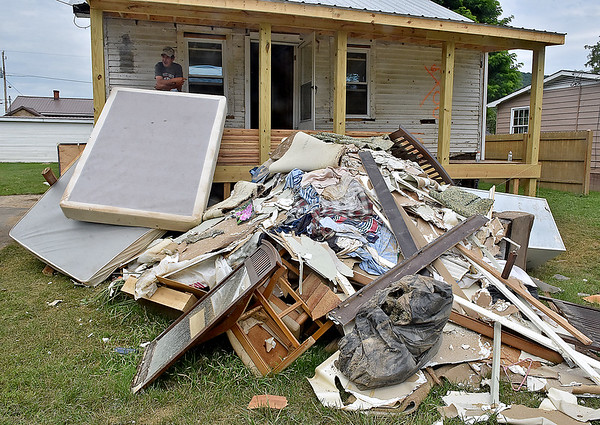 (Brad Davis/The Register-Herald) Rainelle resident Kevin Bowen, upper left, looks on from the front porch of his Fifth Street home as he describes his ordeal while taking a break working on his home Sunday afternoon. Like many in the town, he is now wrestling with the decision to either rebuild his home or relocate somewhere else.