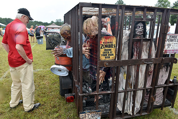 (Brad Davis/The Register-Herald) Another brief rain shower didn't keep attendees from checking out Nitro residents Greg and Sherry Fields' zombie hunter vehicle, which came complete with a trailor of moving zombies at the Friends of Coal Auto Fair Saturday afternoon at the Raleigh County Memorial Airport.