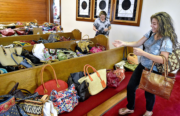 (Brad Davis/The Register-Herald) Young First Baptist Church volunteers Hannah, left, and Brooke Cole bring out another round of donated purses full of items Friday evening at the Neville Street church. By the end of the day, the group had hundreds upon hundreds of purses ready for distribution to areas of the state most affected by last week's flooding.