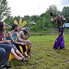 (Brad Davis/The Register-Herald) From left, Jonathan Archie, Ashley Pierce, Colby Elswick, Drew Jobe and Mallory Mann (hidden behind Jobe) are greeted by the stilt-walking Mad Hatter and Alice, also known as Springfield, Missouri's Ryan Hobson and Merisa Vernoy Friday evening at Mountian Music Festival.
