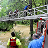 (Brad Davis/The Register-Herald) One at a time, rescue personnel from Fayetteville, Oak Hill and Ansted fire departments use a ladder truck to help stranded volunteers at the Fayette County Humane Society Animal Shelter across the flooded creek Thursday afternoon near Fayetteville. Several volunteers and employees were stranded when flood waters washed away the small bridge at the shelter. In this photo shelter volunteer Anna Bennett (middle on ladder) is escorted to safety.