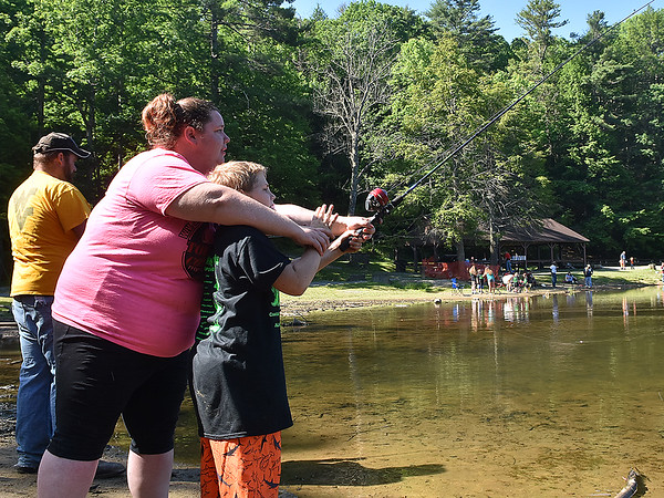 (Brad Davis/The Register-Herald) Matthew Gill, 9, gets a little help casting his line from Samantha Clark during the Kids Fishing Derby Saturday morning at Little Beaver State Park.