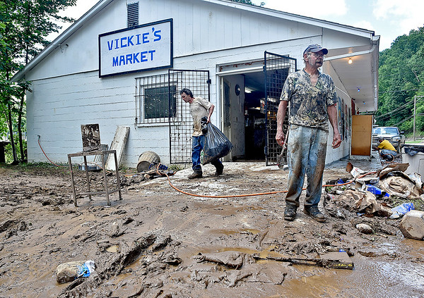 (Brad Davis/The Register-Herald) Richwood resident Roger Rock, right, pauses briefly Friday morning as fellow resident John Ellison, left, continues hauling bags of trash from Vickie's Market, which was completely flooded during Thursday night's disaster.