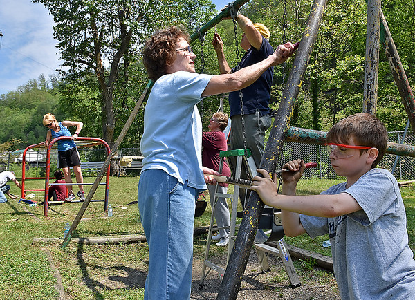 (Brad Davis/The Register-Herald) From right, volunteers John Paul Lusk, 11, John Morgan (ladder), Norma Sneed-Moore (background behind ladder) and Trudy Blackwell, along with several others prep the playground equipment at Mullens Middle School for fresh paint during a Rural Appalachian Improvement League (R.A.I.L.) cleanup day around the town Saturday morning.