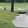 (Brad Davis/The Register-Herald) An area resident manages as best he can while keeping his drains clear as flood waters stream across his property near Fayetteville Thursday afternoon.