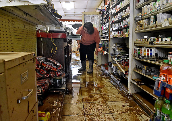 (Brad Davis/The Register-Herald) Oakford Avenue resident Kim Moore helps Vickie's Market co-owner Cornell DeGregory clean up Saturday in Richwood.