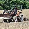 (Brad Davis/The Register-Herald) Milton Kinzer notices the camera and waves as he tills a field to prep it for planting during a Register-Herald visit to the historic farm near Jumping Branch June 8.